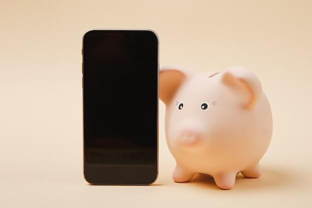 Téléphone mobile de tirelire rose avec écran vide vide isolé sur fond de mur beige. banque d'investissement d'accumulation d'argent ou concept de richesse des services aux entreprises. copiez la maquette publicitaire de l'espace.