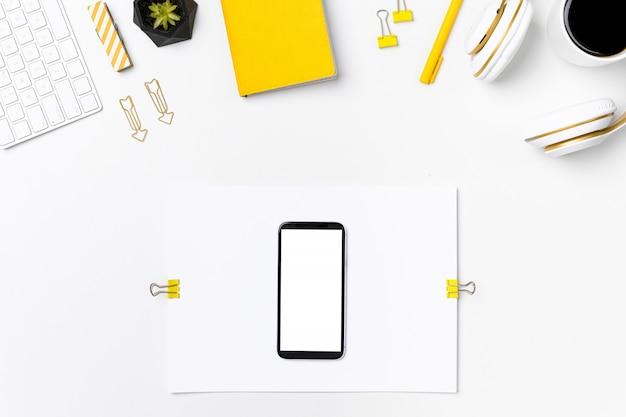Téléphone mobile sur vue de dessus de maquette de lieu de travail de concepteur