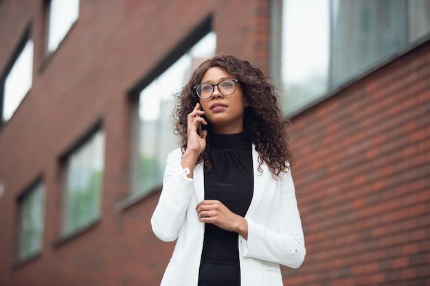 Téléphone parlant. femme d'affaires afro-américaine en tenue de bureau souriante, a l'air confiante et sérieuse, occupée. concept de finance, d'entreprise, d'égalité et de droits de l'homme. belle jeune mannequin, réussie.