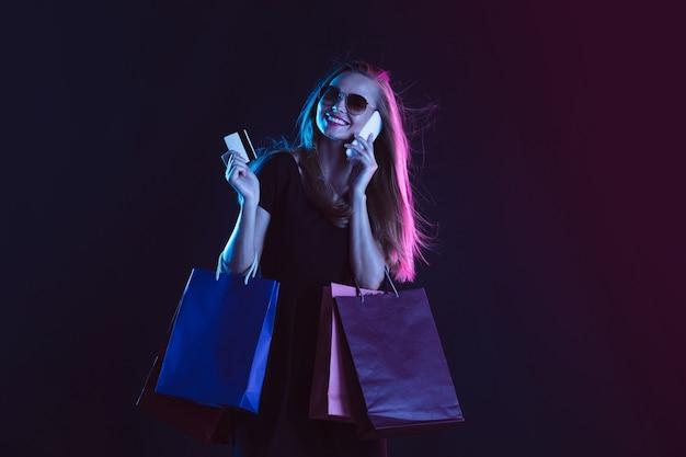 Téléphone parlant avec des sacs à provisions et une carte. portrait de jeune femme en néon sur fond sombre. les émotions humaines, vendredi noir, cyber lundi, achats, ventes, concept financier.