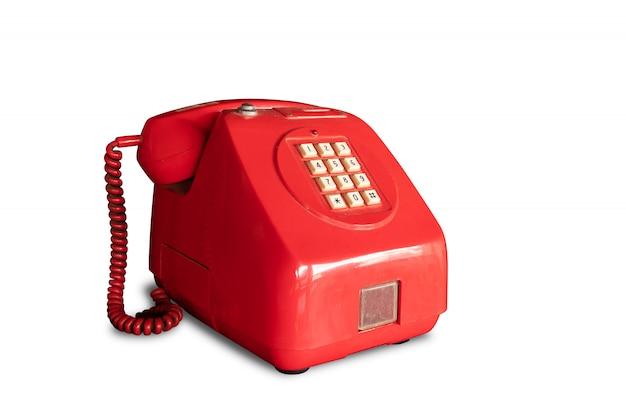 Téléphone payant rétro rouge exploité par des pièces isolées sur blanc