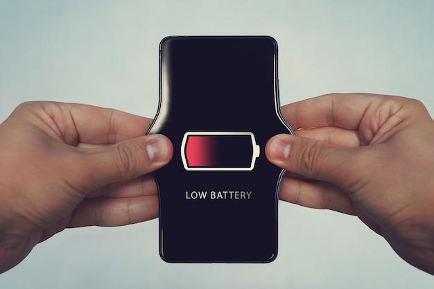 Téléphone portable avec batterie faible à l'écran. tous les graphiques de l'écran sont constitués. augmenter la puissance de la batterie, charge faible. les mains des hommes étirent le téléphone. concept, conception, idée, vision, notion.