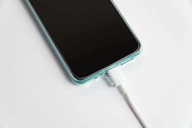 Téléphone portable bleu connecté au câble usb type c - chargement