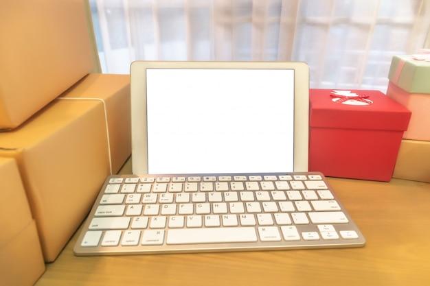 Téléphone portable et boîte d'emballage de colis marron au bureau à domicile. le vendeur de mains prépare le produit prêt à livrer au client. vente en ligne, commerce électronique démarrage du concept d'expédition.