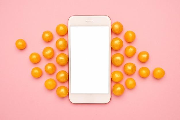Téléphone portable et bonbons jaunes sucrés sur un rose, technologie