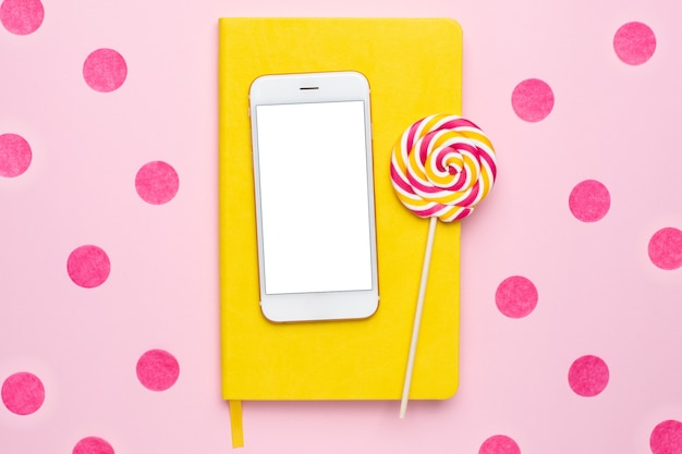 Téléphone portable avec un cahier jaune et une sucette colorée sur rose avec des confettis