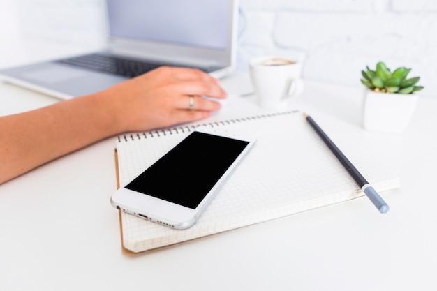 Téléphone portable, carnet et crayon devant une femme à l'aide d'un ordinateur portable