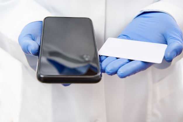 Téléphone portable et carte blanche en plastique sur les mains dans des gants médicaux sur le fond de l'uniforme blanc du médecin. copiez l'espace. concept d'assurance maladie