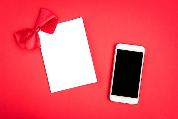 Téléphone portable avec carte de voeux sur rouge.