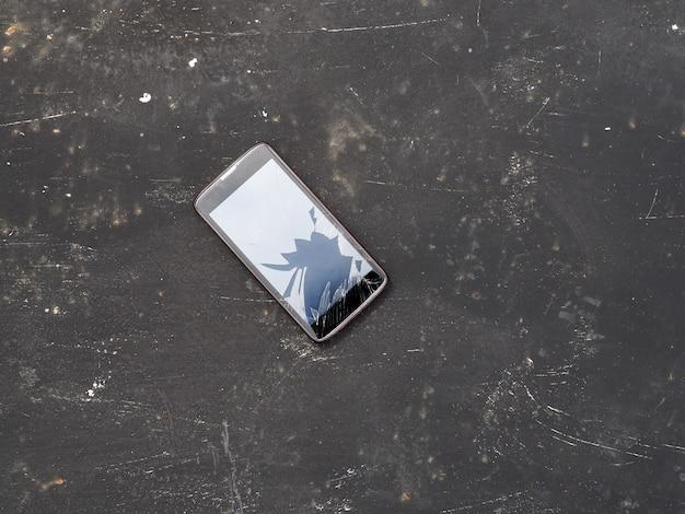 Téléphone portable cassé moderne sur fond noir