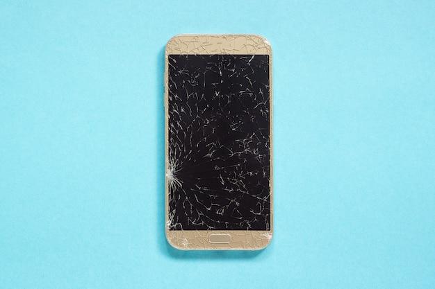 Téléphone portable cellulaire cassé fissures sur fond bleu