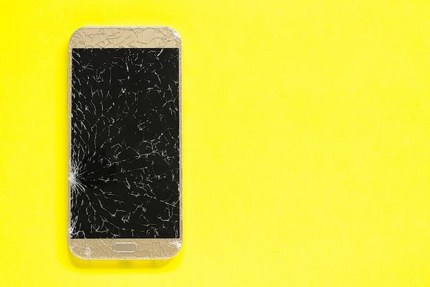 Téléphone portable cellulaire cassé fissures sur fond jaune