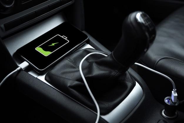 Téléphone portable, charge de la batterie du smartphone, chargement dans la prise de voiture se bouchent
