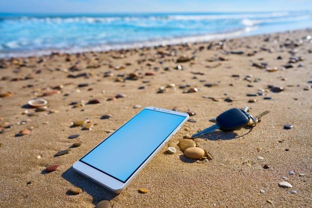 Téléphone portable et clés de voiture sur le sable de la plage