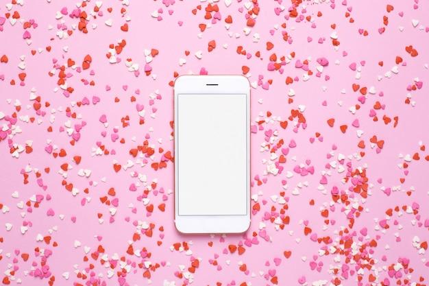 Téléphone portable avec des coeurs roses et rouges sur rose