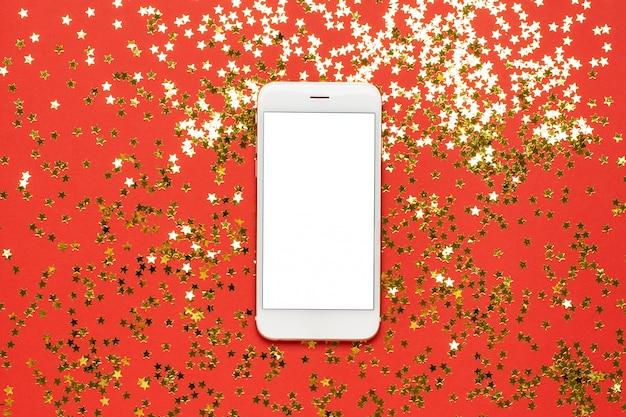 Téléphone portable avec des confettis d'étoiles d'or
