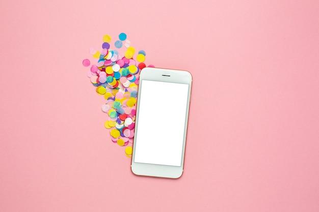 Téléphone portable et confettis multicolores sur une table pastel rose dans un style plat