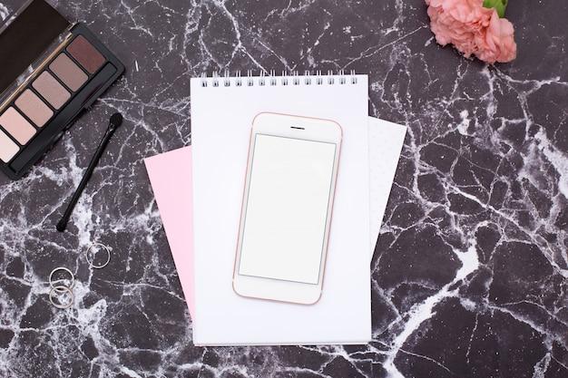 Téléphone portable et cosmétiques sur une table en marbre noir
