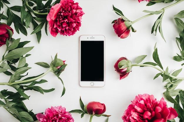 Téléphone portable dans le cadre de fleurs de pivoines roses sur fond blanc. mise à plat, vue de dessus