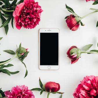 Téléphone portable dans le cadre de fleurs de pivoines roses sur une surface blanche