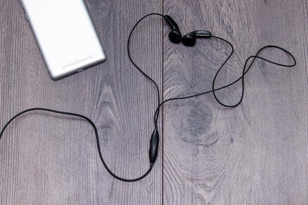 Téléphone portable avec des écouteurs en forme ou coeur sur fond en bois. lay plat, espace de copie.