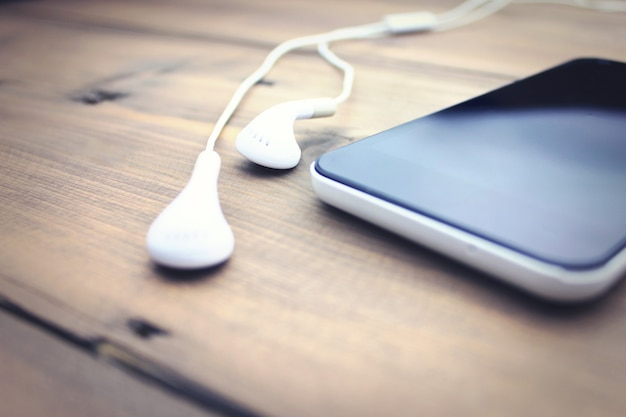 Téléphone portable et écouteurs sur table en bois