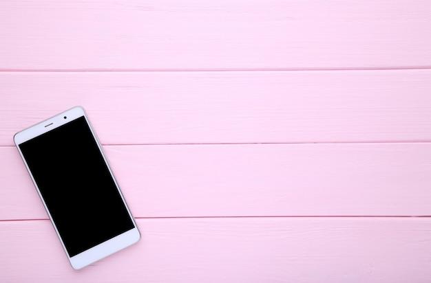 Téléphone portable avec un écran blanc sur fond de bois rose. smartphone sur la table en bois.