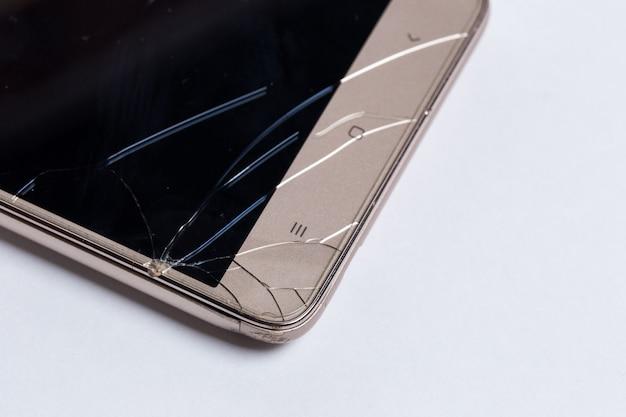 Téléphone portable avec écran cassé sur blanc