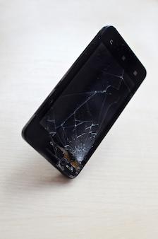 Téléphone portable écran cassé sur fond gris. smartphone assurance et concept de garantie de téléphone portable vue de dessus.