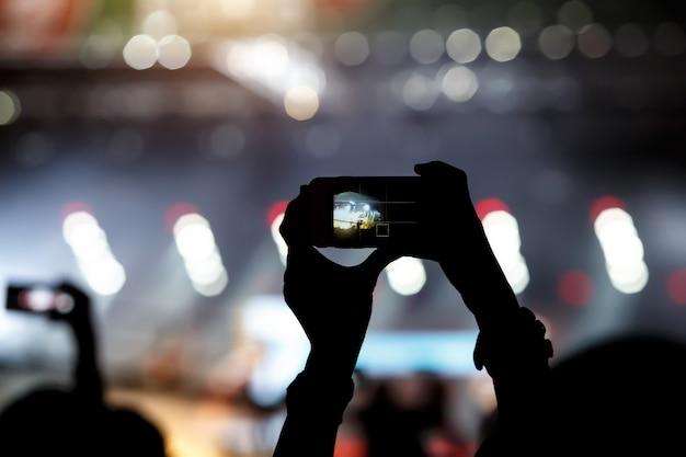 Un téléphone portable entre les mains d'un fan au spectacle de musique d'été. enregistrement de concerts