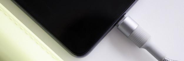 Le téléphone portable est connecté avec un câble à la banque d'alimentation en gros plan