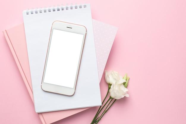 Téléphone portable, fleur blanche et carnet sur rose