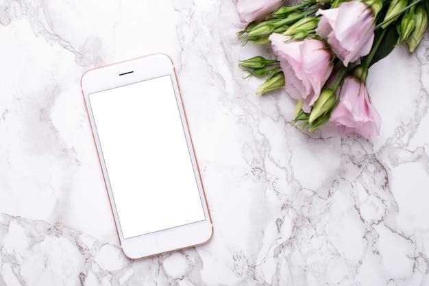 Téléphone portable avec des fleurs roses sur marbre