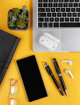 Téléphone portable et gadgets modernes sur une vue de dessus de fond jaune. concept d'entreprise