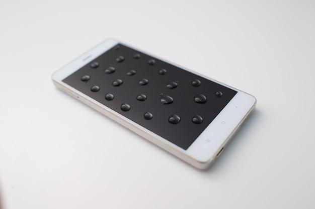 Téléphone portable avec gouttes sur écran oléophobe.