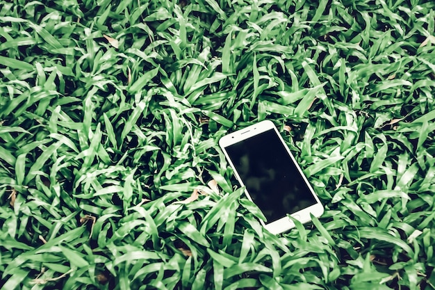 Téléphone portable sur l'herbe verte. travailler à l'extérieur partout style de vie .simplifier la vie avec l'arrière-plan de l'idée de concept technologique .maquette pour le code qr du coupon sur un téléphone intelligent
