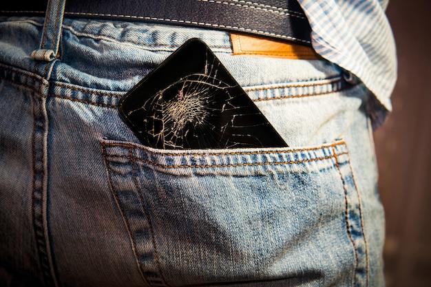 Téléphone portable intelligent noir avec écran cassé dans une poche arrière en denim.