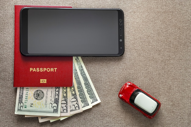 Téléphone portable noir, argent dollars américains billets de banque, passeport et voiture jouet sur copie espace fond, vue de dessus. voyage concept de planification de vacances voyage léger et confortable.
