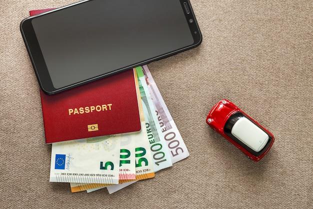 Téléphone portable noir, billets en euros, passeport et voiture jouet