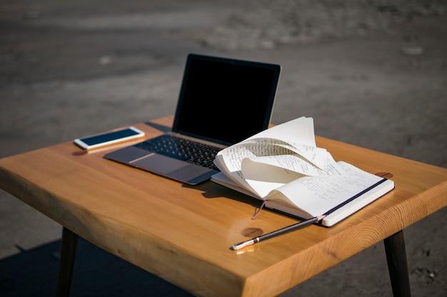 Téléphone portable, ordinateur portable et un crayon sur la table mezzanine. meubles de grenier