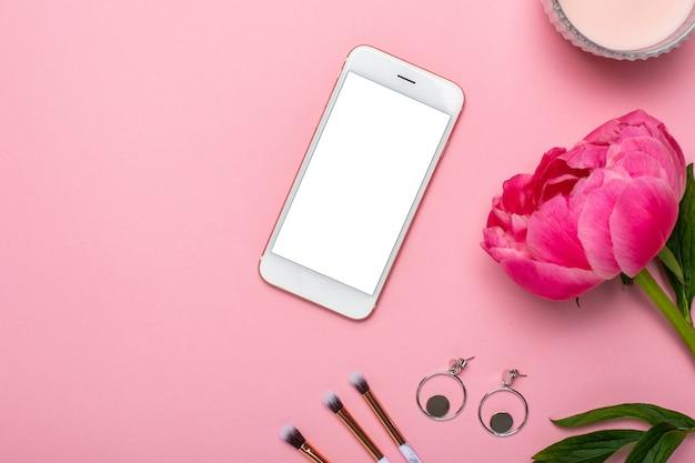 Téléphone portable avec pinceaux de maquillage, boucles d'oreilles et pivoine fleurie sur une table pastel rose dans un style plat. bureau de beauté féminine.