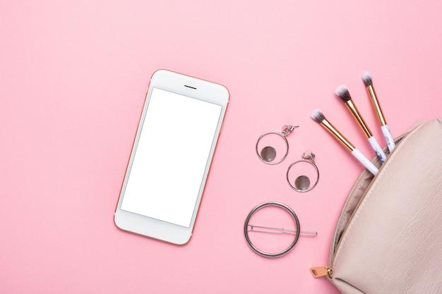 Téléphone portable avec des pinceaux de maquillage et des boucles d'oreilles sur une table pastel rose dans un style plat. bureau de beauté féminine.