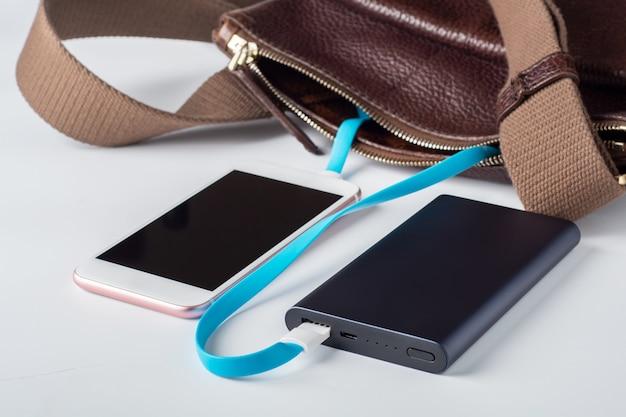 Un téléphone portable pour recharger les appareils mobiles. la banque d'alimentation bleue charge le téléphone
