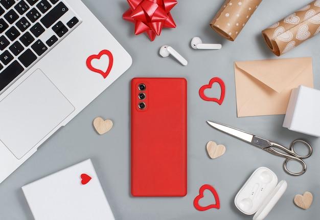 Téléphone portable rouge, coeurs, ordinateur portable, écouteurs, ciseaux, coffrets cadeaux et papier cadeau