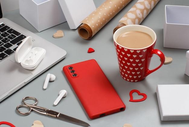 Téléphone portable rouge, coeurs, tasse de café, ordinateur portable, écouteurs, ciseaux, coffrets cadeaux et papier cadeau