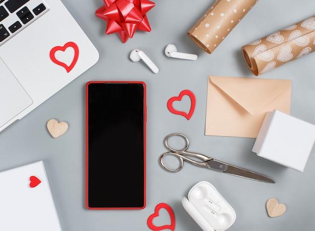 Téléphone portable rouge et décorations de la saint-valentin près d'un ordinateur portable