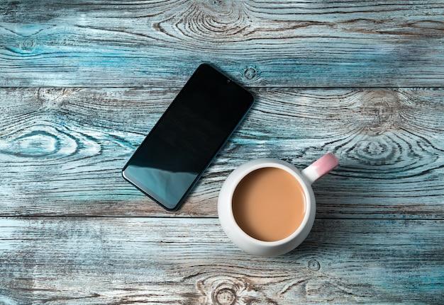 Téléphone portable et une tasse de café sur une table en bois.