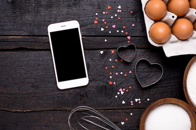 Téléphone portable, ustensiles de cuisine et coeurs sur bois