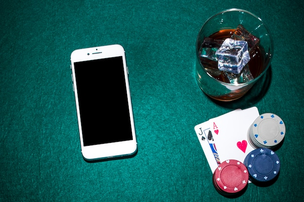 Téléphone portable et verre à whisky avec jack de pique et cartes cardiaques sur table de poker verte