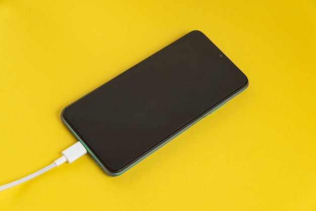 Téléphone portable vert connecté au câble usb type c - chargement